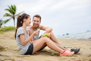 couple on beach eating salad
