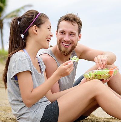 happy couple on beach eating salad